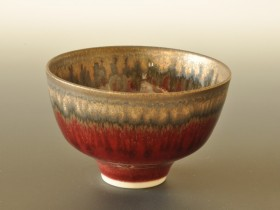 Tiny red and bronze bowl 9cm diameter.